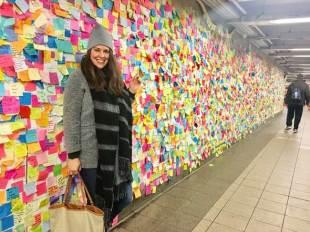 カリフォルニア州ビクタービルで育ったブルック・セルフさんは現在、ニューヨークのマンハッタンで弁護士アシスタントをしている。写真はマンハッタンのユニオンスクエア駅にある「地下鉄セラピー」壁の前で撮影。トランプ氏の大統領当選後に、地元の住民がメッセージを書いてストレスを解消させた。セルフさんは、「私は今でも彼女(クリントン候補)を支持します」と付せんに書いて貼った=2016年12月[本人提供]