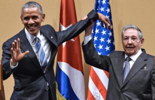 記者会見で、オバマ米大統領(左)の左手を持ち上げるキューバのラウル・カストロ国家評議会議長=2016年3月21日、ハバナ【AFP時事】