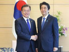 会談前に韓国の文在寅大統領(左)と握手する安倍晋三首相=2018年5月9日、首相官邸【時事】