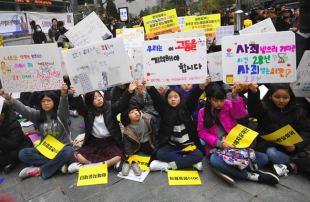 日本大使館前でプラカードを掲げ、慰安婦問題で抗議する支援者=2018年11月21日、ソウル【AFP時事】