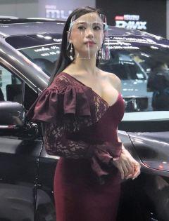 バンコク国際モーターショーで、フェースシールドを着用して自動車をPRするコンパニオン=2020年7月14日【時事通信社】