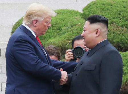 30日、板門店の南北軍事境界線の韓国側で、握手するトランプ米大統領(左)と北朝鮮の金正恩朝鮮労働党委員長(EPA時事)