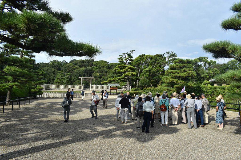 仁徳天皇陵前で参拝するツアー客ら=13日、堺市