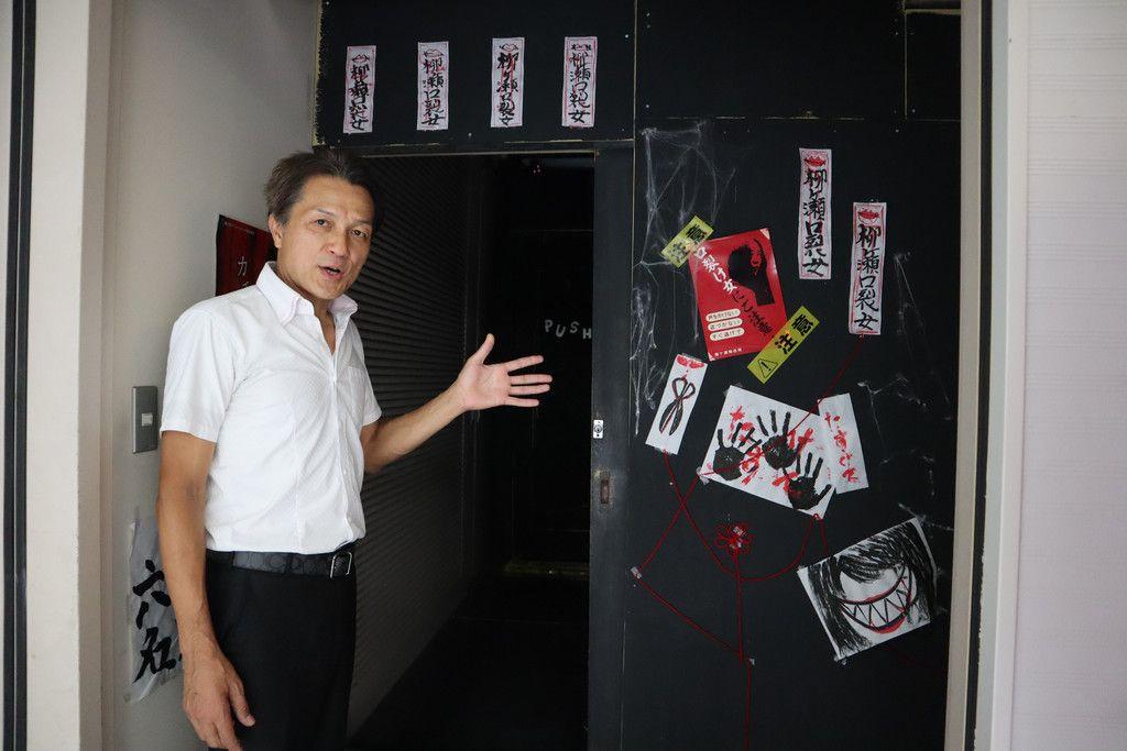 「口裂け女」をテーマにしたお化け屋敷の入り口を指す、主催団体の広報担当を務める稲垣康雄さん=12日午後、岐阜市