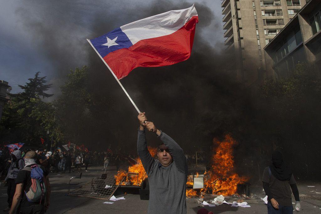 29日、チリの首都サンティアゴで、国旗を振る反政府デモ参加者(AFP時事)