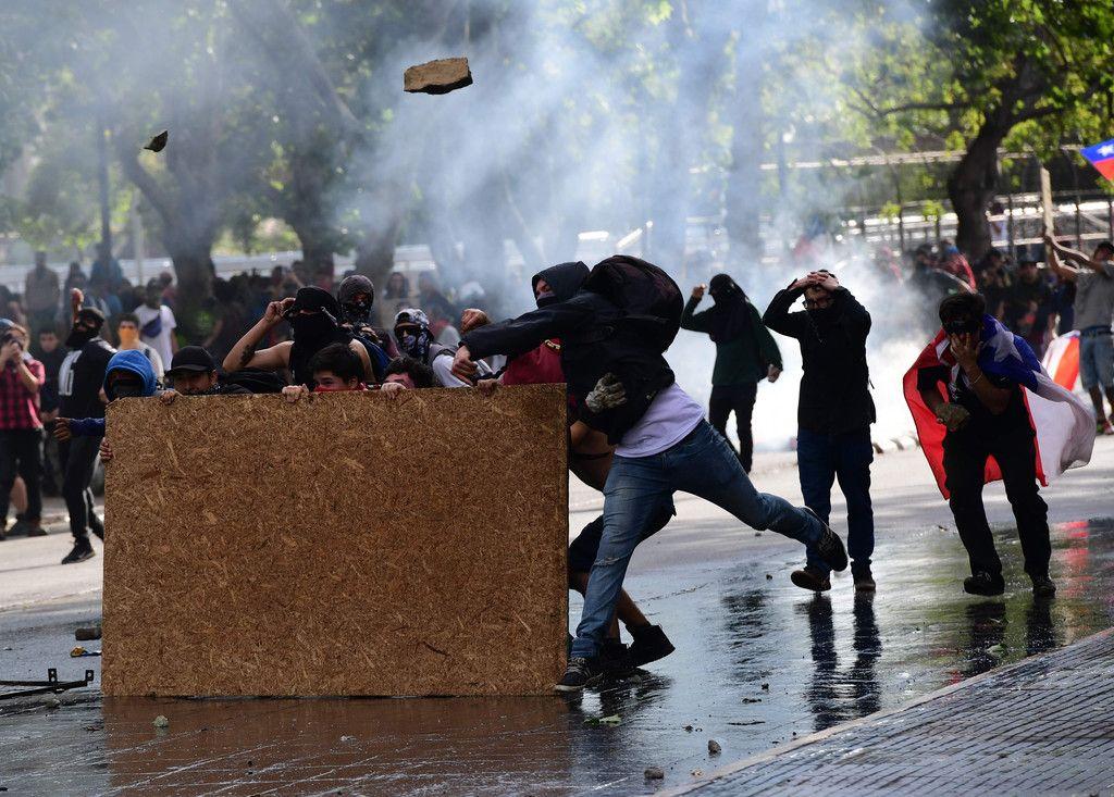 29日、チリの首都サンティアゴで、投石する反政府デモ隊(AFP時事)