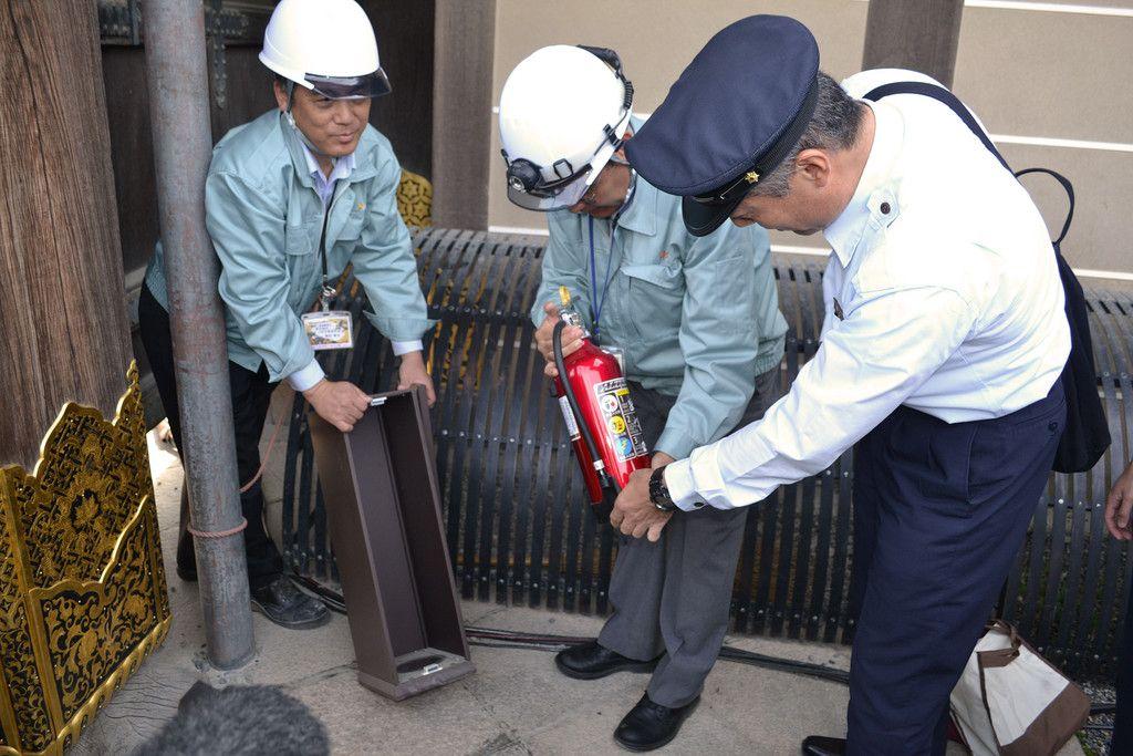 二条城の消火器を点検する消防署員(右)ら=31日午前、京都市中京区