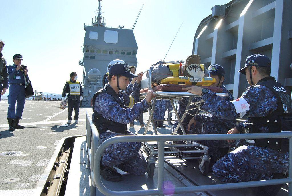 原子力防災訓練で、護衛艦「いせ」の弾薬用昇降機を使い、急患役の馬渡島民を艦内の医務室に運ぶ乗員ら=30日午前、佐賀県唐津市
