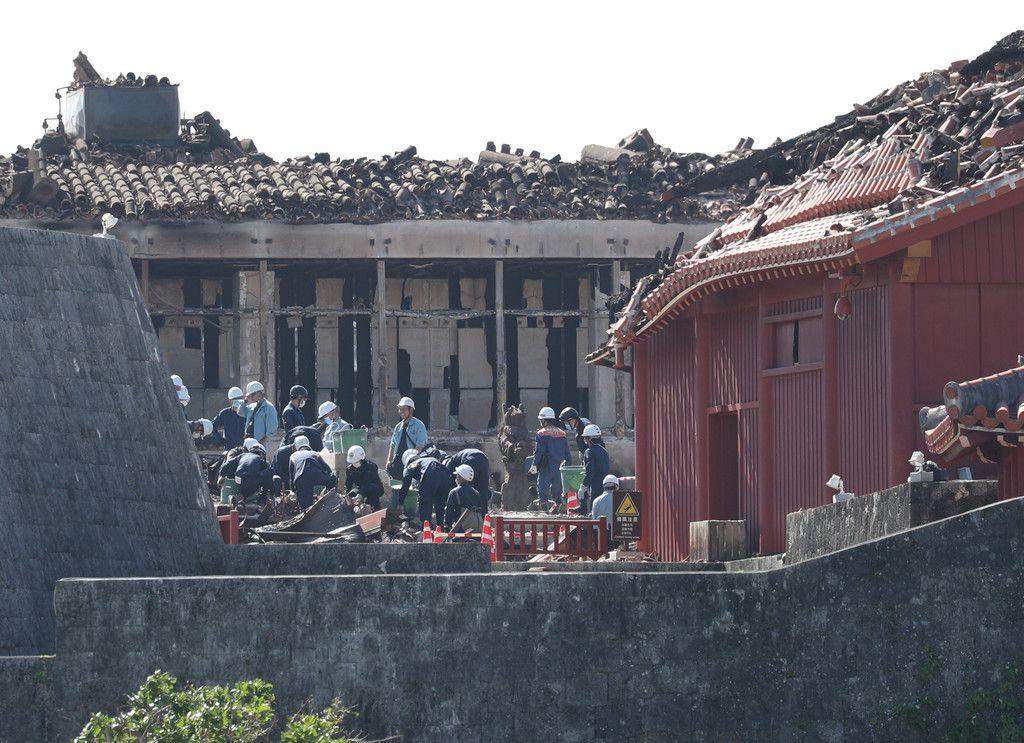 焼失した首里城の正殿前に残った大龍柱(中央右)付近を調べる消防隊員ら=11月2日、沖縄県那覇市