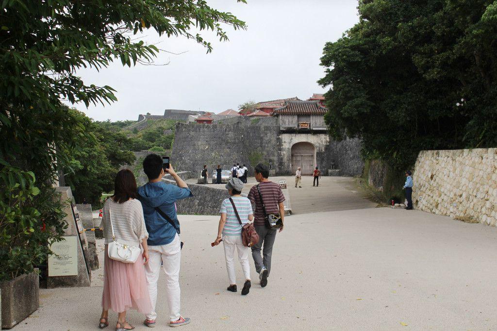 首里城公園を散策する観光客。奥は火災で焼失した正殿など=11月25日、那覇市