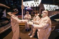 中国湖北省武漢市で防護服を配るボランティアら=26日(AFP時事)