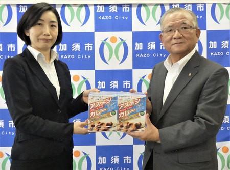 花咲徳栄高校の教諭から「アスメシカレー」を受け取る大橋加須市長(右)=7月17日午後、同市役所