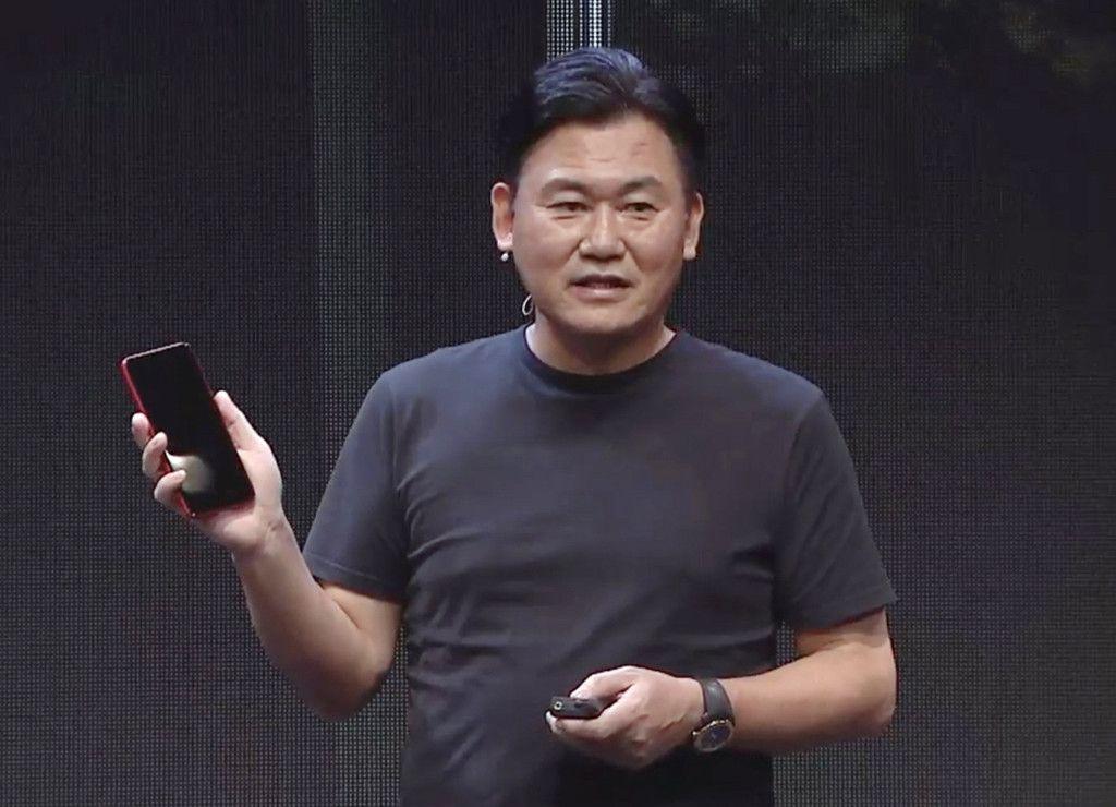 楽天が独自開発した5G対応端末を手に、5Gサービス開始のオンライン会見に臨む同社の三木谷浩史会長兼社長=30日午後